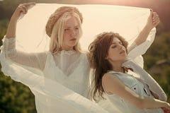 Doppeltes Brautset auf weißen Rosen Frauen mit Stroh windt auf blondem und Brunettehaar Lizenzfreies Stockfoto