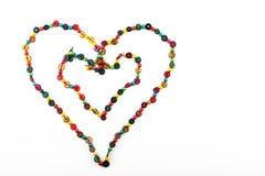 Doppeltes Herz formte die bunte Perlenhalskette, die auf Weiß lokalisiert wurde Lizenzfreies Stockfoto