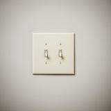 Doppeltes Lightswitch auf weißer Wand Lizenzfreie Stockfotografie