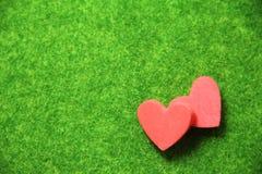Doppeltes rotes Herz auf grünem Boden vor Valentinsgruß lizenzfreie stockbilder