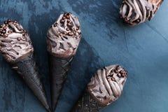 Doppeltes SchokoladeEiscreme mit schwarzen Waffel-Kegeln lizenzfreie stockfotos