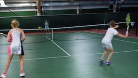 Doppeltes Team des Jungen und des Mädchens, die Tennis mit erfahrenem Frauenspieler spielen stock video footage