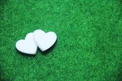 Doppeltes weißes Herz auf grünem Boden vor Valentinsgruß lizenzfreie stockfotografie