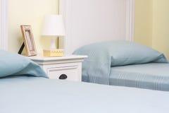Doppelzimmer mit unterschiedlichen Betten und Lampe Stockfotografie