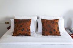 Doppi cuscini marroni in camera da letto Fotografia Stock