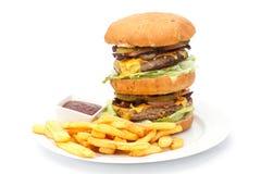 Doppi hamburger e patatine fritte del formaggio con ketchup fotografia stock libera da diritti