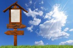 Doppi segni di legno direzionali su cielo blu Fotografie Stock