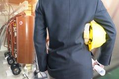 Doppia esposizione del casco della tenuta dell'ingegnere su sala elettrica FO immagine stock libera da diritti
