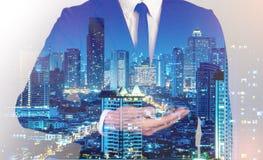 Doppia esposizione del fondo della città dell'uomo di affari di successo HOL della mano Fotografia Stock Libera da Diritti