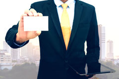 Doppia esposizione dell'uomo d'affari che tiene e che mostra biglietto da visita in bianco sul fondo della città Immagini Stock Libere da Diritti