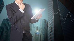 Doppia esposizione dell'uomo d'affari facendo uso della compressa con il grafico finanziario Fotografie Stock