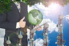 Doppia esposizione dell'uomo d'affari facendo uso della compressa con il pla della terra verde Fotografia Stock Libera da Diritti