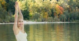 Doppia esposizione della donna con le mani afferrate dal lago contro gli alberi Fotografie Stock