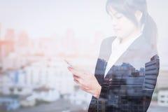 Doppia esposizione della donna di affari che per mezzo dello Smart Phone con la città della sfuocatura fotografie stock