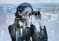 Doppia esposizione della donna di affari con binoculare e la megalopoli Immagine Stock