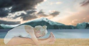 Doppia esposizione della donna di misura che fa yoga alla spiaggia Fotografia Stock