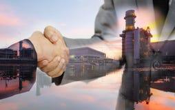 Doppia esposizione della stretta di mano del doppio dell'uomo di affari e della fabbrica di generazione elettrica Fotografia Stock