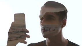Doppia esposizione dello smartphone di usi dell'uomo e di bella spiaggia Doppia esposizione delle onde del mare e dell'uomo video d archivio