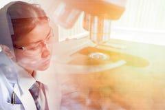 Doppia esposizione di giovani medico e microscopio immagini stock libere da diritti