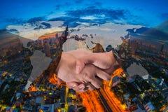 Doppia esposizione di una stretta di mano dell'uomo d'affari sul mondo Carto globale Fotografia Stock