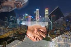 Doppia esposizione di una stretta di mano dell'uomo d'affari sulla vista aerea della CIT Fotografia Stock