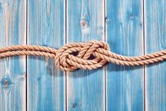 Doppia figura della corda naturale otto nodi su legno blu Immagine Stock Libera da Diritti