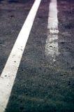 Doppia linea bianca stagionata sulla strada asfaltata Fotografia Stock