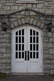 Doppie porte bianche incorniciate con vecchio lavoro di pietra fotografia stock