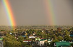 Doppio arcobaleno sopra la città, zona residenziale, doppio arcobaleno sopra il cielo blu, primo piano, arcobaleno immagine stock