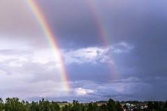 Doppio arcobaleno sopra la foresta e le case immagine stock