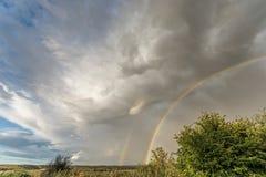Doppio arcobaleno sotto le nuvole di pioggia minacciose fotografia stock