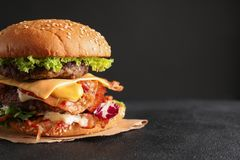 Doppio hamburger saporito con bacon sulla tavola immagine stock