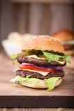 Doppio hamburger sul bordo di legno Fotografia Stock