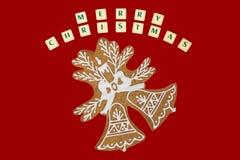 Doppio pan di zenzero delle campane di Natale con desideri su rosso Immagini Stock Libere da Diritti