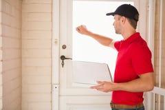 Doręczeniowego mężczyzna mienia pizza podczas gdy pukający na drzwi obraz stock