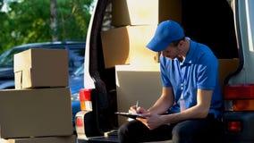 Doręczeniowego mężczyzny transportu podsadzkowi dokumenty, siedzi blisko Samochodu dostawczego Bagażnik, obowiązki zdjęcie royalty free