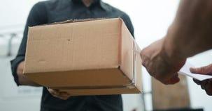Doręczeniowy mężczyzna dostarcza pakunek klient, zamyka up przy i boksuje i zbiory