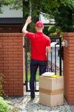 Doręczeniowy mężczyzna dostarcza pakunki stwarzać ognisko domowe Zdjęcia Royalty Free