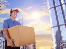 Doręczeniowy mężczyzna i karciany pudełko dostarcza w miasto budynku zdjęcia royalty free