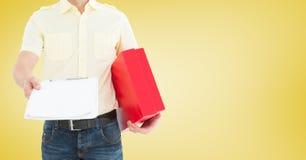 Doręczeniowy mężczyzna trzyma schowek i pakuneczek przeciw żółtemu tłu Obraz Stock