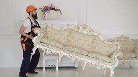 Doręczeniowy mężczyzna w ochronnego hełma poruszającej kanapie w pięknym białym wewnętrznym pokoju Meblarski doręczeniow zbiory