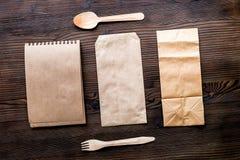 Doręczeniowy ustawiający z papierowymi torbami i flatware na drewnianym tle t obraz stock