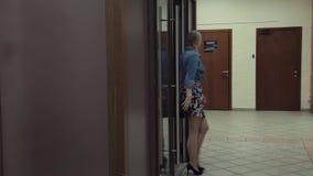 Dor и прогулки молодой привлекательной женщины открытое стеклянное в коридор офиса сток-видео