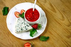 Dor Blue cheese and strawberry, berry jam and mint leaves close-up, on a wooden background, a top view of the place for the text royalty free stock photography