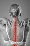 Dor da espinha, mulher com dor lombar e dor no pescoço, foto preto e branco com espinha dorsal vermelha foto de stock