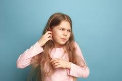 A dor da orelha Menina adolescente em um fundo azul Expressões faciais e conceito das emoções dos povos foto de stock