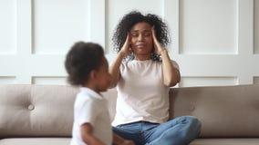 Dor de cabeça africana virada forçada do sentimento da mamã cansado de crianças ativas vídeos de arquivo