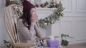 Dor de cabeça asiática da sensação da mulher envolvida no sopro geral cinzento o nariz e o tecido do uso ao encontrar-se na cadei vídeos de arquivo