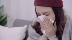 Dor de cabeça asiática da sensação da mulher envolvida no sopro geral cinzento o nariz e o tecido do uso ao encontrar-se no sofá  filme