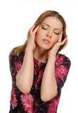 Dor de cabeça - cabeça da terra arrendada da mulher nova na dor Fotografia de Stock